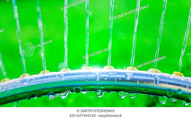 Lawn sprinkler spaying water over green grass. Motion blur. Select focus