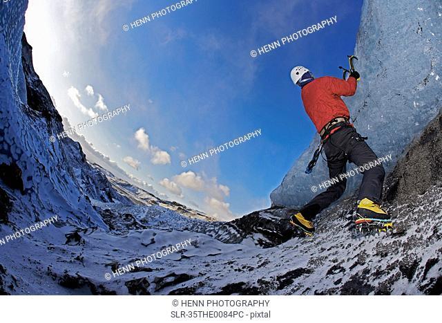 Man climbing glacier with ice picks