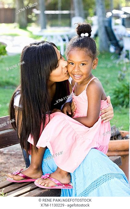 A mixed race mother kisses her smiling daughter on the cheek