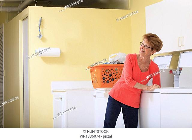 Senior woman taking laundry out of a washing machine