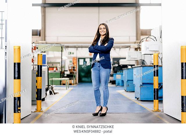 Confident woman working in high tech enterprise, standing in factory workshop with arms crossed