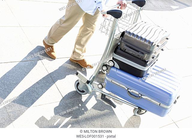 Man pushing baggage cart at the airport