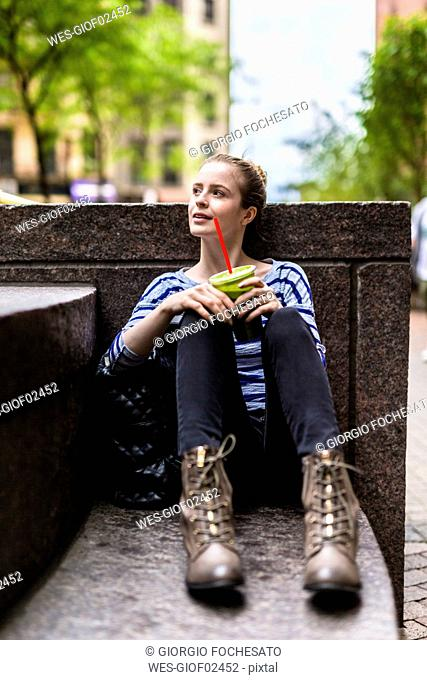USA, New York City, woman having a break drinking a smoothie in Manhattan