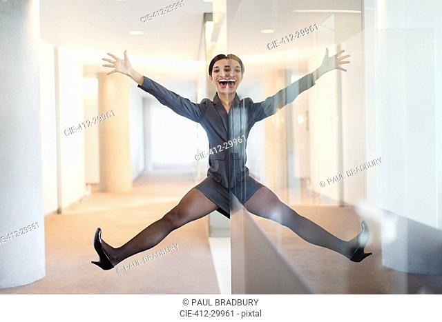 Symmetrical reflection portrait of playful businesswoman with arms and legs apart in office corridor