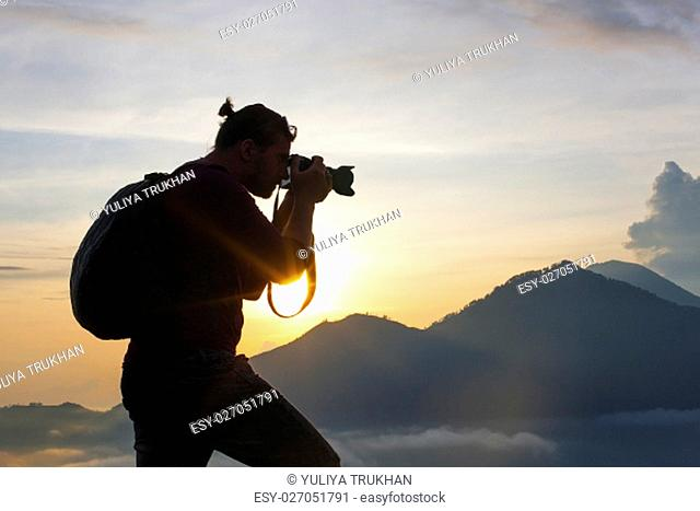 Photographer Hiker walking along, takes pictures and meets sunrise on the mountain - Stock image
