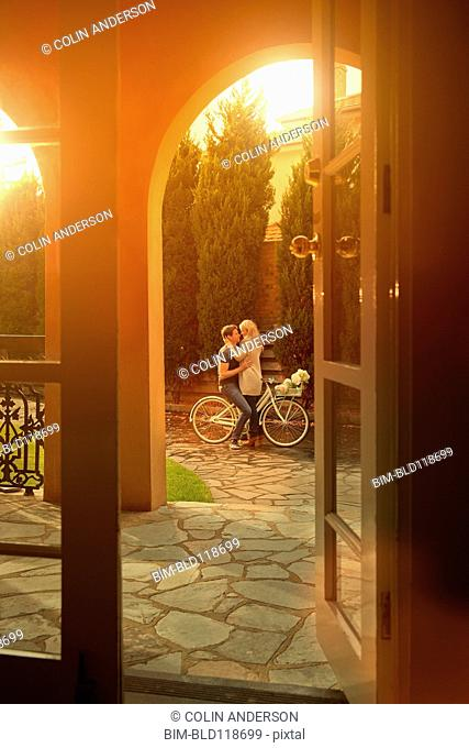 Caucasian couple hugging on bicycle