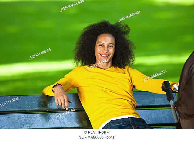 Smiling young man with afro hair relaxing on bench