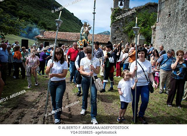 Three women in jeans, lead the modest procession of Loreto. Llanes, Asturias, Spain