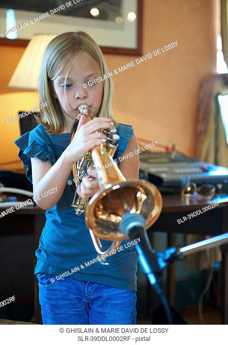 Girl playing trumpet into microphone