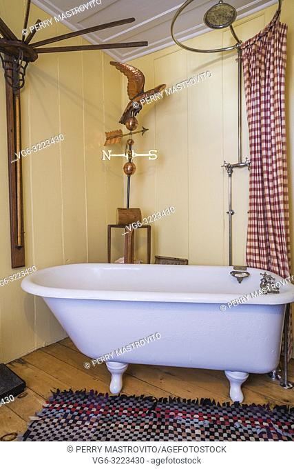 Freestanding clawfoot bathtub in main bathroom with yellow walls on ground floor inside an old 1835 fieldstone house