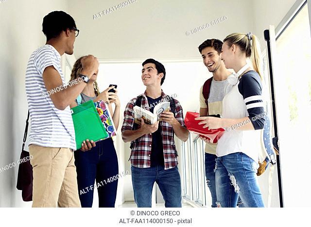 Students chatting in school corridor between classes