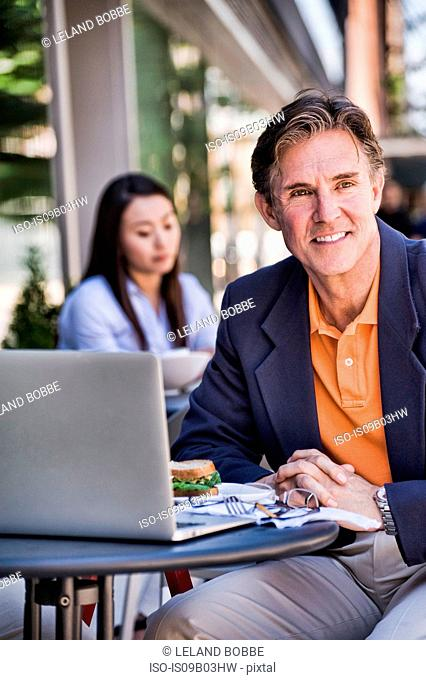 Businessman sitting outside cafe, using laptop