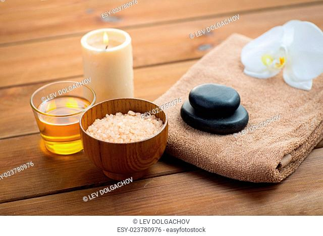 beauty, spa, body care, natural cosmetics and concept - close up of pink salt with honey in glass and bath towel on wooden table