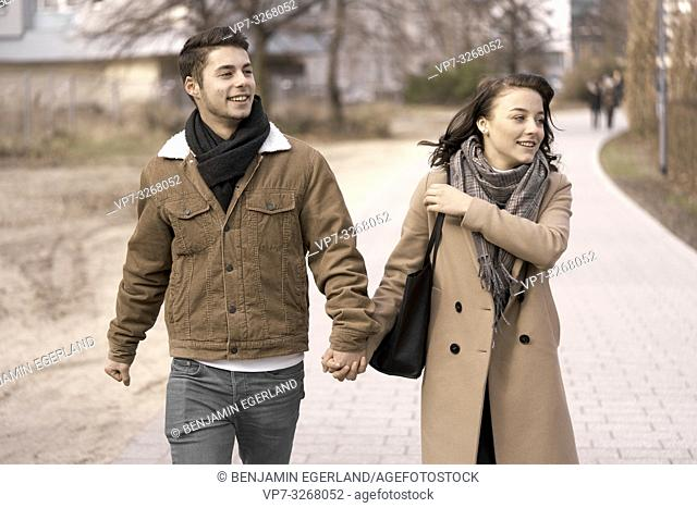 young teenage couple walking hand in hand, outdoors in park in city, in Cottbus, Brandenburg, Germany