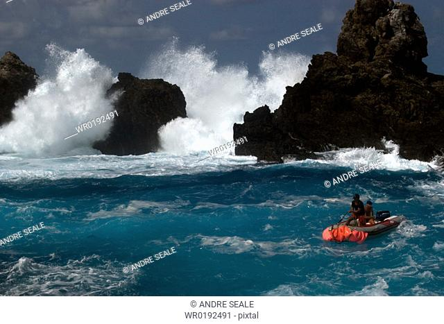 Small boat and waves crashing over St Peter and St Paul's rocks, Brazil, Atlantic Ocean