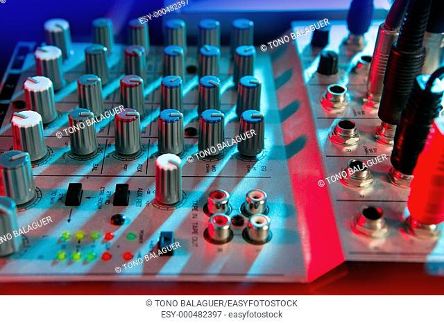 Audio mixer music desk under colorful lights equipment