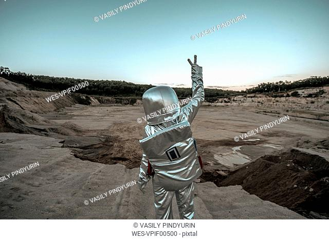 Spaceman making peace sign on a nameless planet
