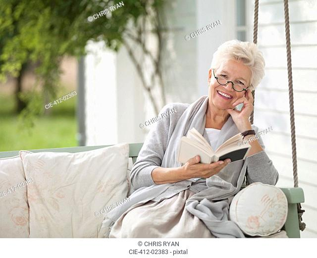 Woman reading in porch swing