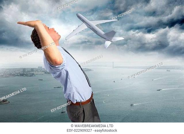 Composite image of businessman standing with hands up