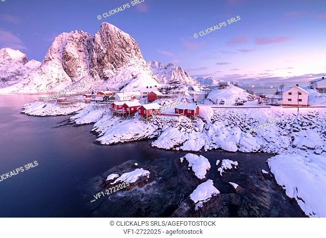 Pink sunrise on snowy peaks surrounded by the frozen sea around the village of Hamnoy Nordland Lofoten Islands Norway Europe