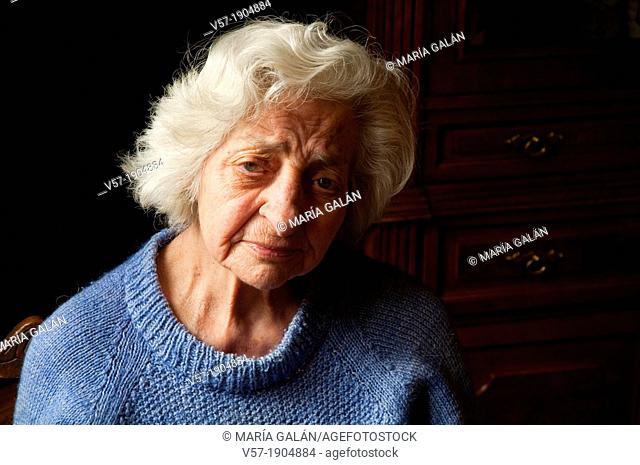 Portrait of old woman at home, looking at the camera. Close view