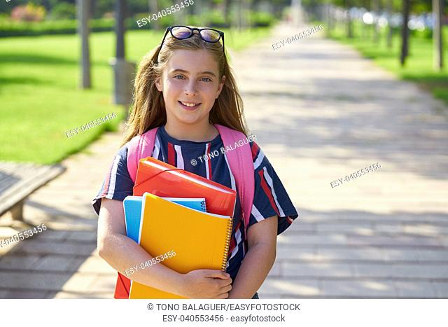 Blond kid student girl notebook and backpack in the park back to school