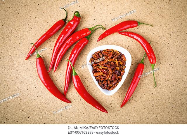 Fresh and dried red hot chili peppers on wooden table