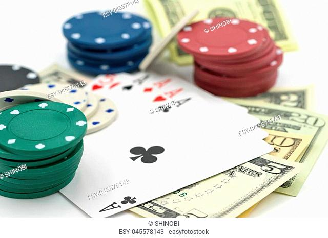 A great combination of four aces, dollars and casino playing chips lie on a white surface