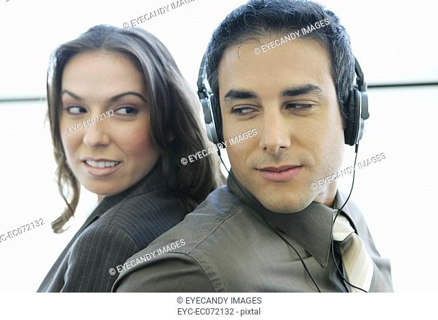 Young business couple relaxing at airport with headphones
