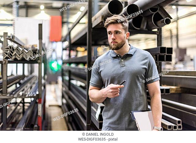 Man with clipboard on factory shop floor looking around