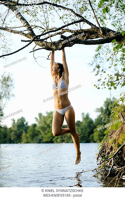 Woman wearing a bikini hanging on tree branch over a lake
