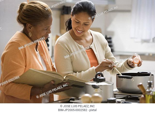 Women cooking with a cookbook in the kitchen