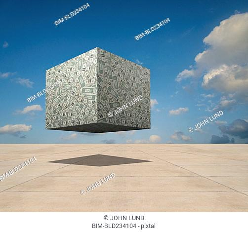 Cube of dollars floating over concrete