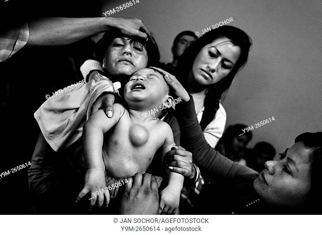 A Colombian mother holds her baby boy, having a tumor in his chest, during the religious healing ritual performed at a house church in Bogota, Colombia