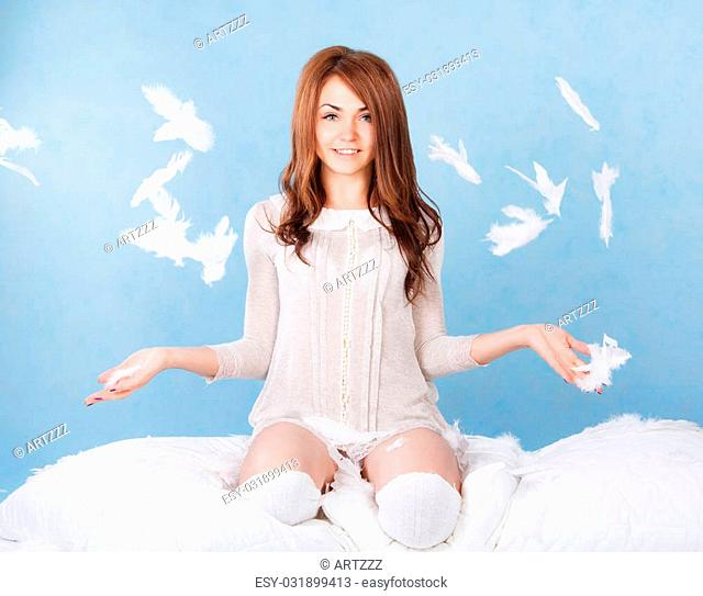 Beautiful young woman in a bed dropping the feathers over blue background