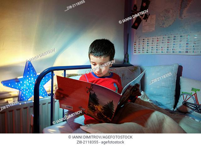Young boy,reading a bedtime story in his bed