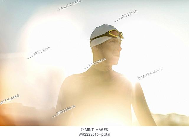 A swimmer in a wet suit, swimming hat and goggles