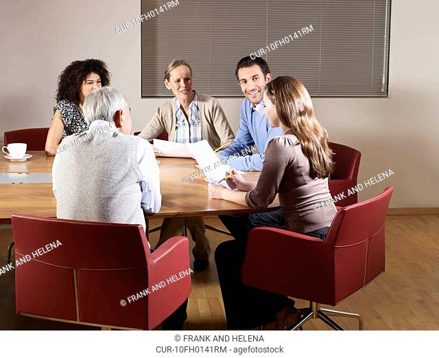 Group of people sitting around conference table having a meeting. They are all smiling and listening to a young woman reading