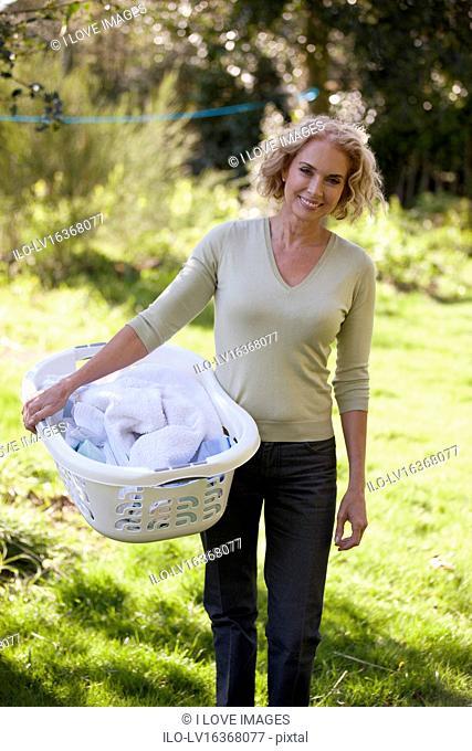 A mature woman holding a laundry basket outside