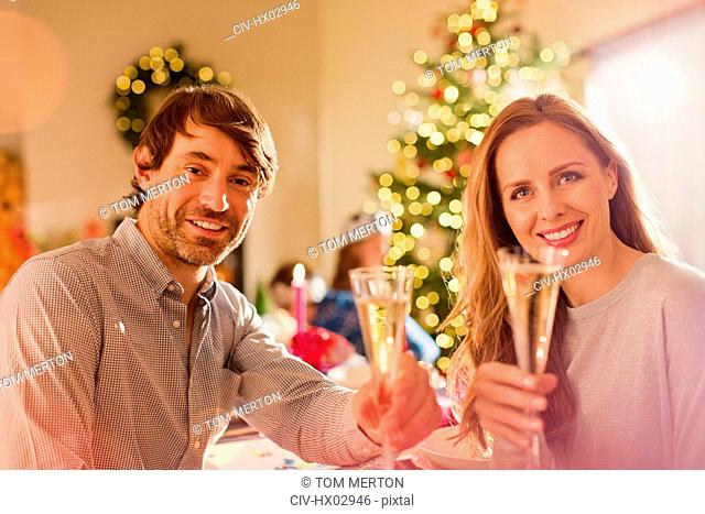 Portrait smiling couple toasting champagne flutes at Christmas dinner table