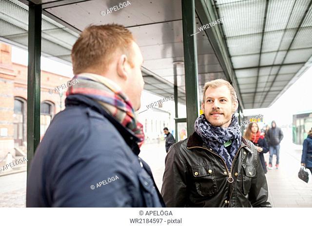Mid adult men conversing at bus stop