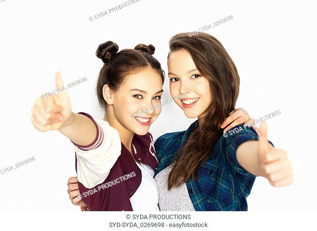 happy teenage girls hugging and showing thumbs up