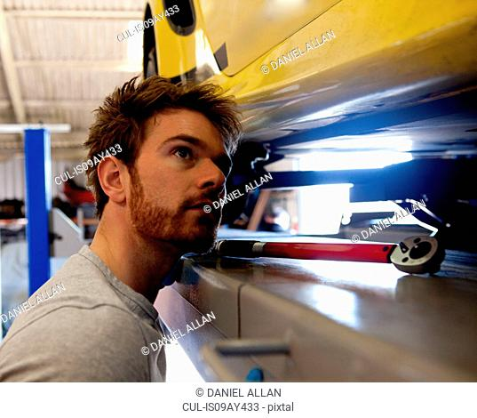 Male mechanic looking underneath sports car