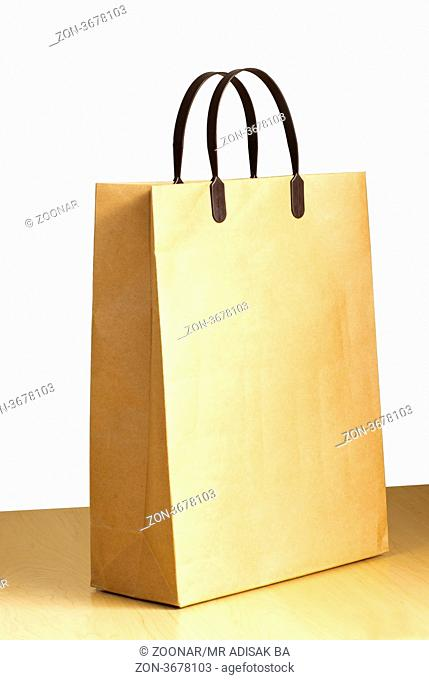 Paper bag on wooden floor against the white wall