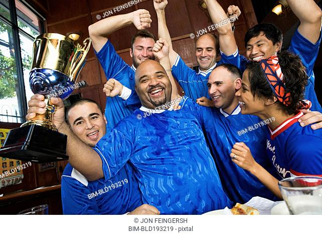 Cheering teammates and man holding trophy