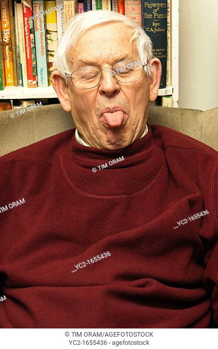 A senior elderly man in his 80's pulling a funny face at home in England , Britain , Uk