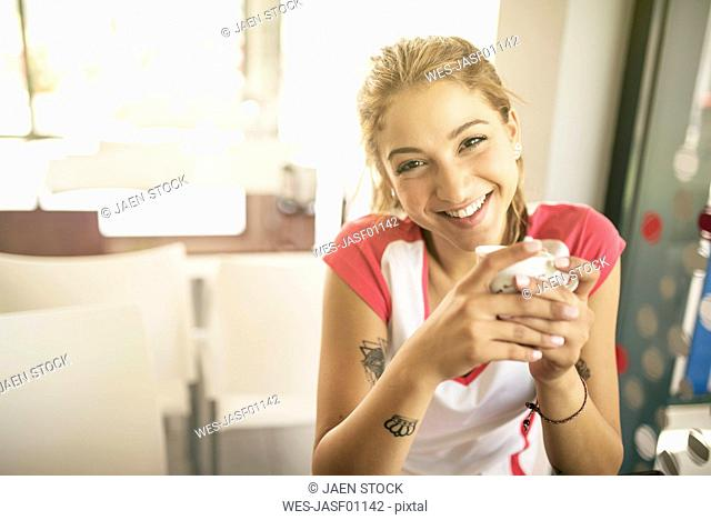 Smiling young woman in a cafe drinking coffee