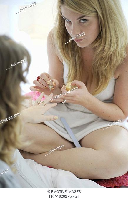 Two young women manicuring