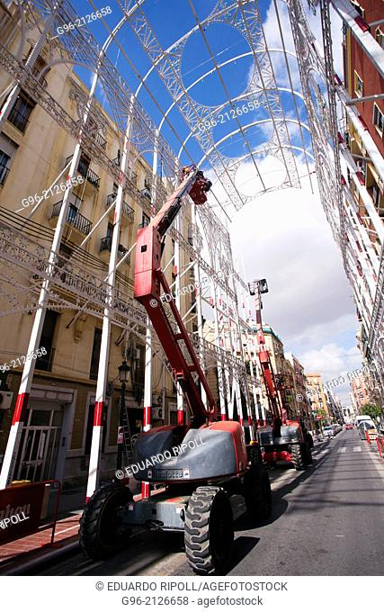 workers mounting lights decorations at the street in Valencia, Spain, before fallas