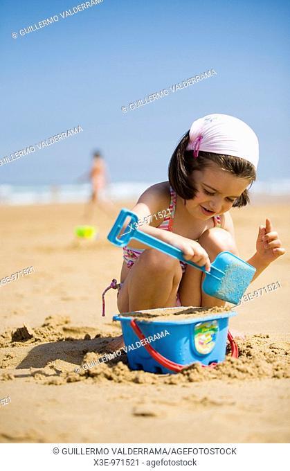 Niña jugando con la arena en la playa